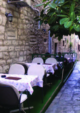 "A typically narrow street in Korcula with tables at an outdoor restaurant. Perhaps two feet of ""street"" remained to the right of the tables!"