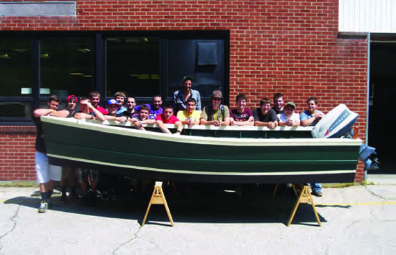 Students in the Tiverton High School marine-trades program show off a 16-foot skiff that they built. © rimta.org