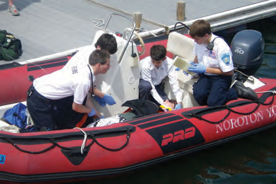 Suspecting a spinal injury, the Emergency Medical Technicians from Darien EMS Post 53 checked the stricken sailor's vital signs and stabilized him before transporting him to an ambulance